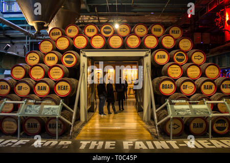 DUBLIN, IRELAND - FEBRUARY 7, 2017- People visiting the interior of the Guinness StoreHouse in Dublin. Wooden barrels of beer - Stock Photo