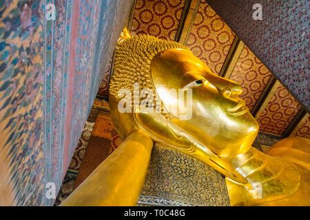Giant golden reclining Buddha statue. Wat Pho temple, Bangkok, Thailand.