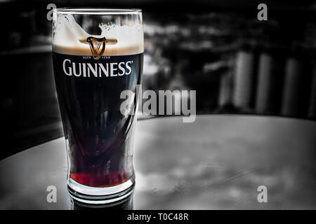DUBLIN, IRELAND - FEBRUARY 7, 2017- Pint of Guinness on a stand almost ready to drink inside the Guinness Storehouse - Stock Photo