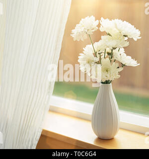 Fresh flowers in vase on windowsill with sheer fabric curtains window coverings. Simple, natural, contemporary home interior decor background elements - Stock Photo