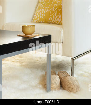 Modern living room interior decor with comfortable chair and pillow, table with teacup and slippers on white sheepskin rug. Relaxing at home. - Stock Photo