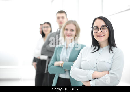 confident businesswoman standing in front of his business team - Stock Photo