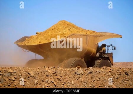Gold mine operation in open gold mine pit with large haul truck leaving with dirt - Stock Photo