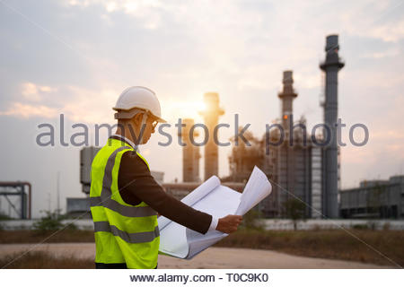Engineer in uniform and helmet on of background the Construction Site power plant - Stock Photo