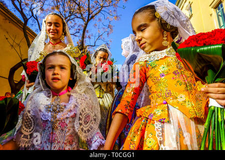 Valencia Fallas festival, Kids, Children in festive folk costumes in parade march to the Virgin Mary with flowers to her honor, Spain - Stock Photo