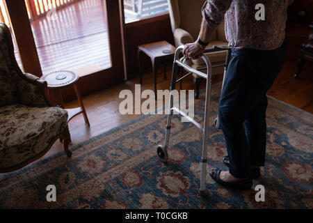Active senior woman walking with walker in living room at home