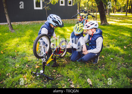 Teamwork. big family three Caucasian children brothers are learning to repair a bicycle, use tools in helmets same clothes, against of building up on - Stock Photo