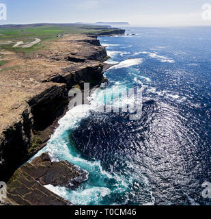 Stunning overhead drone shots of the wild coast of Northern Scotland. High cliffs and waves crash on the rugged shoreline. - Stock Photo