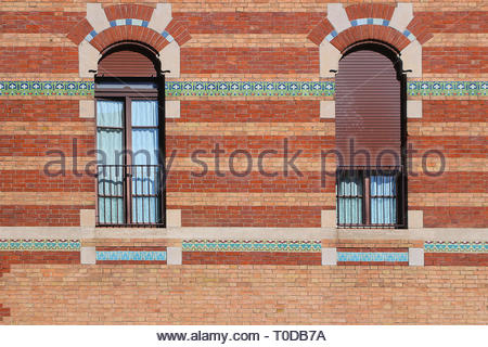 Windows in red brickwall decorated with beautiful ornamental tiles - Stock Photo
