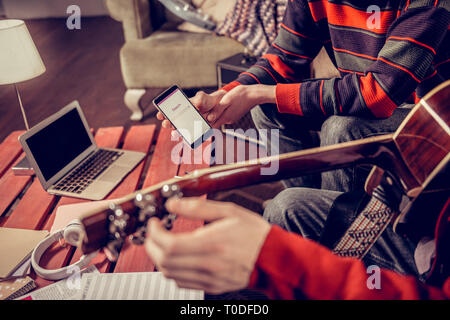 Close up of two musicians searching for some melody in the Internet - Stock Photo