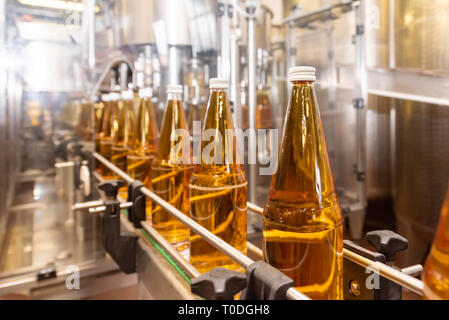 Filling  glass bottles with juice. Bottling of drinks. bottling plant - Stock Photo