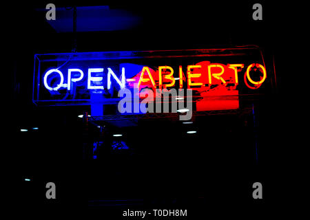 Neon shop 'Open' (In Spanish and English) store sign at night in street with copy space - Stock Photo