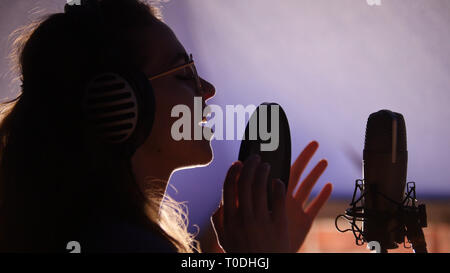A young woman in glasses singing in the studio - Stock Photo