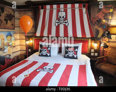 Adults double bed and décor in Premium Pirate Rooms at the hotel at LEGOLAND Windsor Resort UK with welcoming balloon and badge for child's birthday - Stock Photo