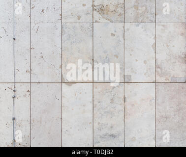 Full frame background of a modern and a bit broken wall or building exterior made of abstract stone slabs. - Stock Photo