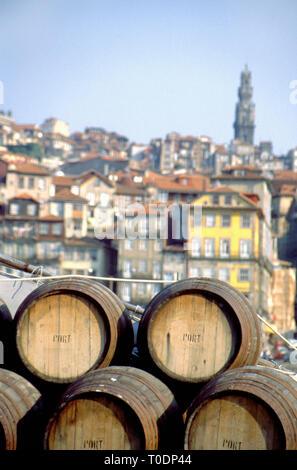Port wine barrels on a boat on River Douro with Vila Nova de Gaia in the background, Porto, Portugal - Stock Photo