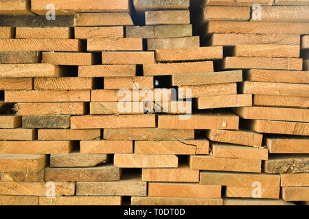 Stacked long wooden yellow planks in warehouse, closeop details - Stock Photo