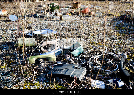 Various kind of waste laying on the ground, telephones, remote, cables, plates, iron, glass, jars - Stock Photo