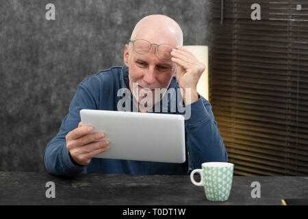 a senior businessman using tablet, he is having difficulties and vision problems - Stock Photo