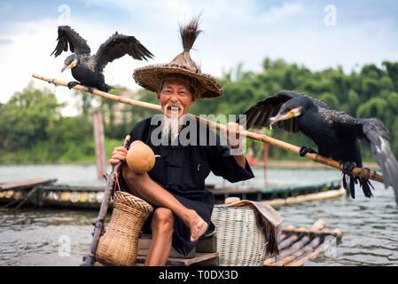 Yangshuo, China - July 27, 2018: Traditional cormorant fisherman on a bamboo rafts on Li river in Yangshuo near Guilin in China - Stock Photo