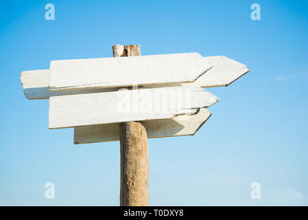 empty white wooden sign board against clear blue sky on sunny day by coast - Stock Photo
