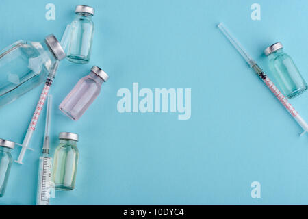 Vials and syringes on blue - Stock Photo