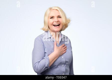 Senior caucasian woman with blonde hair in blue shirt smiling posing at studio. - Stock Photo