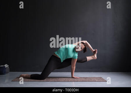 Young woman wearing sportswear practicing yoga in studio,natural light. - Stock Photo