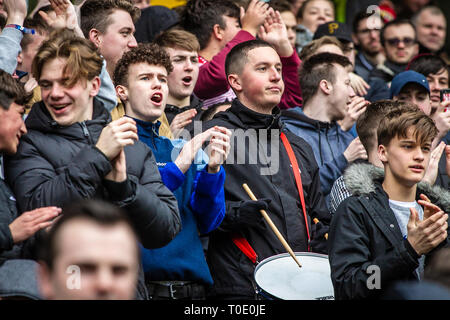 English football club fans and supporters watching match and playing drum - Stock Photo