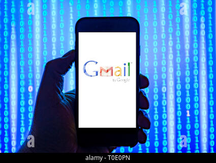 Person holding smart phone with Google Gmail email logo displayed on the screen. - Stock Photo