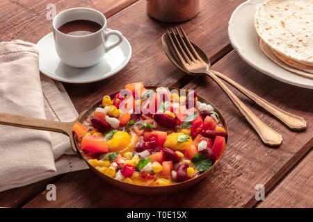 Mexican breakfast food. Huevos rancheros, the fried eggs, with the pico de gallo salad, hot chocolate, and tortillas - Stock Photo