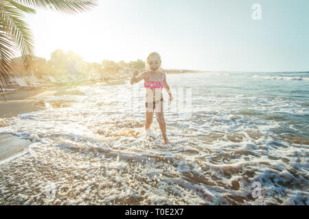 Happy little child girl playing on sea beach and having fun