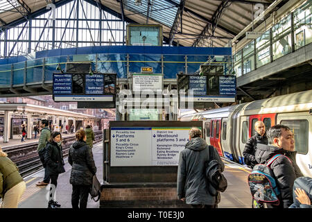 People waiting on the platform  for a District Line train at  Earls Court Underground Station , London SW5 - Stock Photo