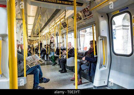 People sitting and standing on a on a S7 stock District Line train on The London Underground, London - Stock Photo