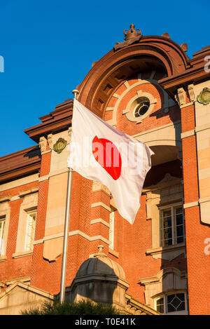 Tokyo Station old brick facade with Japan Nation Flag waving in front of it - Stock Photo