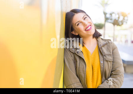 Beautiful young woman smiling confident and cheerful leaning on yellow wall, walking on the street of the city on a sunny day Stock Photo