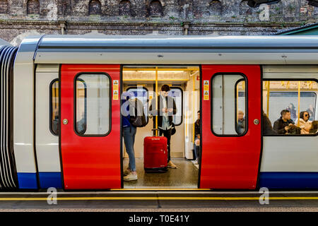 People boarding a District Line/Circle Line train at Sloane Square Underground station - Stock Photo