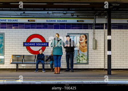 A family waiting for a train at Sloane Square underground station , London SW1 - Stock Photo