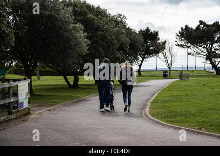 Young couple pushing child through the park in a pushchair,  the father is pushing the stroller - Stock Photo
