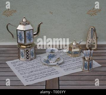 English tea set, silver-plated teapot on a silver stove, spoon vase, sugar bowl and sugar spoon and metronome for music on a sheet of music - Stock Photo