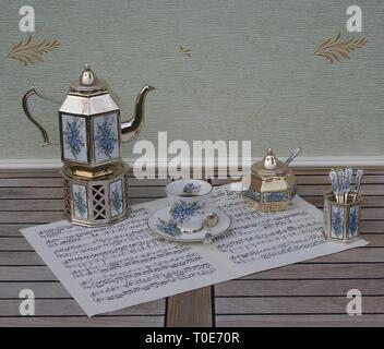 English tea set, silver-plated teapot on a silver stove, spoon vase and teaspoon, sugar bowl and sugar spoon on a sheet of music - Stock Photo