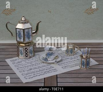 English teacup and saucer, silver-plated teapot on a silver stove, spoon vase, teaspoon and cream jug on a sheet of music - Stock Photo