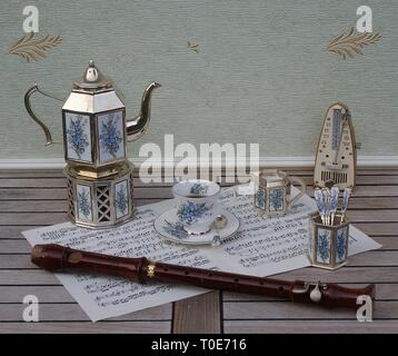 English teacup and saucer, silver-plated teapot, spoon vase, teaspoon, cream jug and metronome for music and a block flute on a sheet of music - Stock Photo