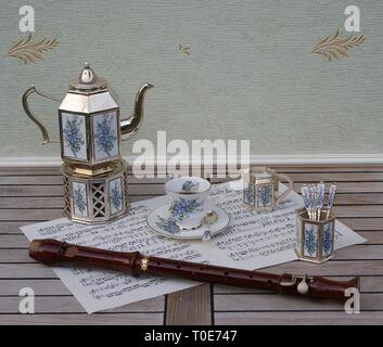 English teacup and saucer, silver-plated teapot on a silver stove, spoon vase, teaspoon and cream jug and a block flute on a sheet of music - Stock Photo