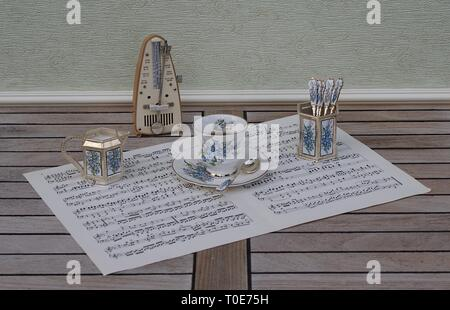 English teacup and saucer, spoon vase, teaspoon and cream jug and metronome for music on a sheet of music - Stock Photo