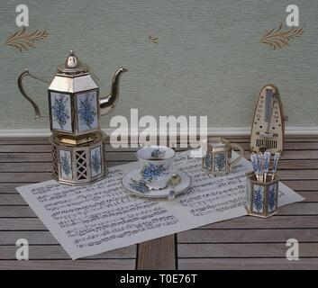 English teacup and saucer, silver-plated teapot on a silver stove, spoon vase, teaspoon and cream jug and metronome for music on a sheet of music - Stock Photo