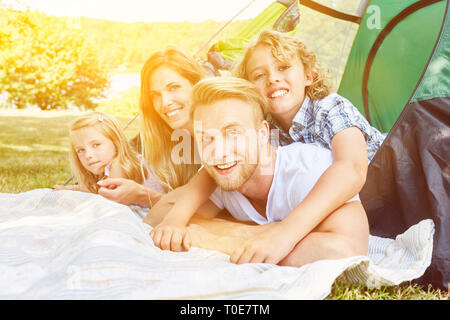 Happy family with two children in the tent while camping in the summer looks on map - Stock Photo