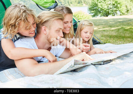 Family with two children in tent are looking at a map on camping holiday - Stock Photo
