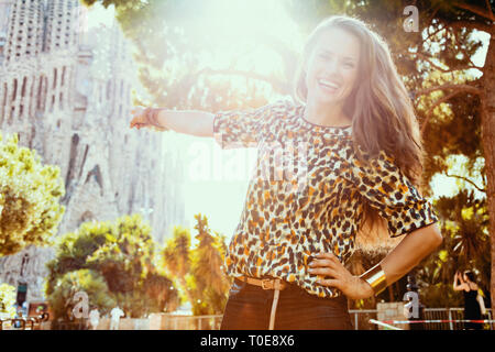 Barcelona - August, 05, 2015: smiling elegant solo traveller woman with long brunette hair in jeans and blouse pointing at La Sagrada Familia in Barce - Stock Photo