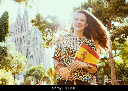 Barcelona - August, 05, 2015: smiling elegant solo traveller woman with long brunette hair in jeans and blouse with Spanish flag against La Sagrada Fa - Stock Photo